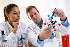 Two students of chemistry looking at molecular model and making Royalty Free Stock Images
