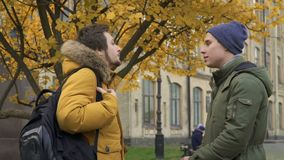Two students discuss something standing near university. Two students stands in park near the university. Friends are discussing some educational material. Young stock footage