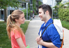 Two students in discussion. Outside in a park on the campus with meadow and trees in the background Royalty Free Stock Image