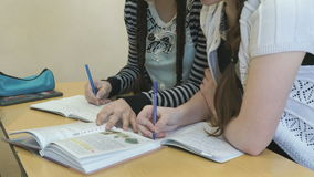 Two students flip pages of textbook at lesson. Two students sitting at the desk flip the pages of textbook at the lesson stock video footage