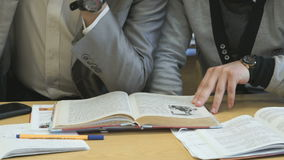 Two students flip pages of textbook at lesson. Two students sitting at the desk flip the pages of textbook at the lesson stock footage