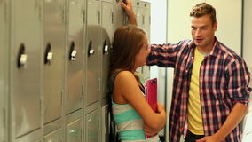 Two students flirting in the hallway beside lockers stock video