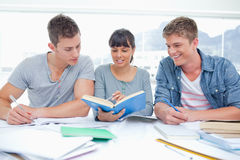 Two students getting help from a female student Royalty Free Stock Image