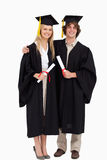 Two students in graduate robe shoulder to shoulder Stock Images
