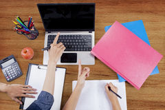 Two students hand pointing at laptop. Close up of two students hand doing homework together and pointing at the laptop screen with stationery on the table Stock Photography