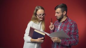 Two Students Have a Friendly Discussion. Two teenager students have a friendly study discussion holding books on red background stock footage
