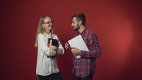Two Students Have a Friendly Discussion. Two teenager students have a friendly study discussion holding books on red background stock video