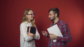 Two Students Have a Friendly Discussion. Two teenager students have a friendly study discussion holding books on red background stock video footage