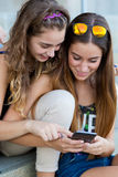 Two students having fun with smartphones after class. Royalty Free Stock Images