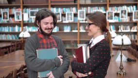 Two Students Talking. Two students having pleasant talk in library, slim woman and well-built man chatting in front of bookshelves, holding books and study stock video footage