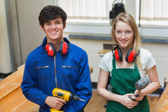 Two students holding a driller and a hammer Stock Photos