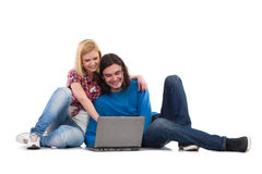 Two students with laptop. Smiling girl and boy sitting on the floor and using laptop. Full length studio shot isolated on white Royalty Free Stock Photo
