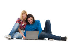 Two students with laptop. Smiling girl and boy sitting on the floor and using laptop. Full length studio shot  on white Royalty Free Stock Images