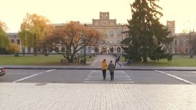 Two students are late to the university. On lectures. Two guys are running to the entrance of campus through the autumn park and road. Camera slowly moves up stock footage