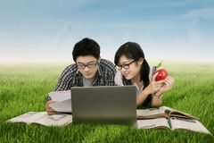 Two students learning on the grass. Portrait of two Asian college students lying on the grass while studying together with books and laptop Stock Images