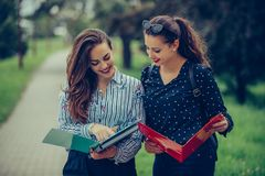 Two students learning reading a notebook and commenting in the street royalty free stock photo