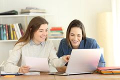 Two students learning together on line. Comparing notes with a laptop at home Royalty Free Stock Image