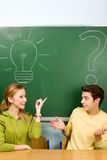 Two students with light bulb and question mark