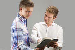 Two students look a book Stock Photography