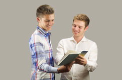 Two students looking at a book while having fun Stock Images