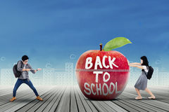 Two students moving a big apple Stock Photography