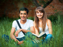 Two students in park on grass with book outdoors Royalty Free Stock Photo