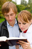Two students reading a book Stock Images