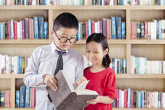 Two students reading book in library Royalty Free Stock Photography