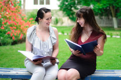 Two students reading books and laughing Stock Image