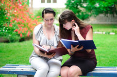 Two students reading books outdoors Stock Images