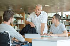 Two students reading in library with senior teacher Royalty Free Stock Photography