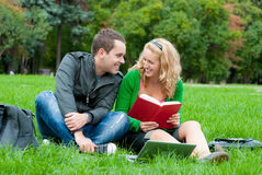 Two students relax and talking. On the grass in the park Royalty Free Stock Photography