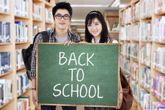 Two students showing a text of back to school Stock Photos