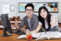 Two students shows thumbs up in the class Royalty Free Stock Photography