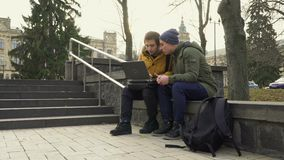 Two students with laptop in park. Two students sits in the park and discuss something looking on laptop. Friends talks with each other and have a conversation stock footage