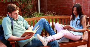 Two students sitting on a bench revising. On college campus stock footage