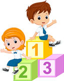 Two students sitting on the numbers blocks Stock Photos