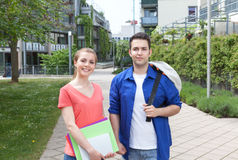 Two students standing on the campus. With university building in the background Stock Images
