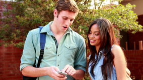 Two students standing and looking at smartphone. On college campus stock video