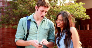 Two students standing and looking at smartphone. On college campus stock footage