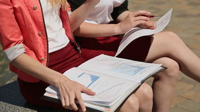 Two students study together with notes on his knees, sitting in the park. Closeup. stock video footage