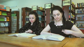 Two students studying books at library stock footage