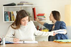 Two students studying doing homework at home. Two students studying together doing homework at home Royalty Free Stock Image