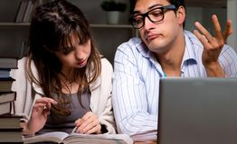 Two students studying late preparing for exams royalty free stock photography