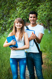 Two students studying in park with book outdoors Stock Images