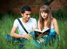 Two students studying in park on grass with book outdoors Royalty Free Stock Images