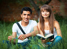 Two students studying in park on grass Royalty Free Stock Photography
