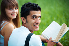 Two students studying in park on grass Stock Photos