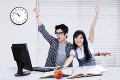 Two students studying and raise hands together Royalty Free Stock Photo
