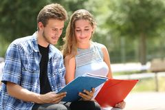 Two students studying together in a campus park. Two concentrated students studying together reading notes in a campus park stock photography